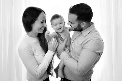 a family portrait in black and white with both mum and dad holding baby, all smiling