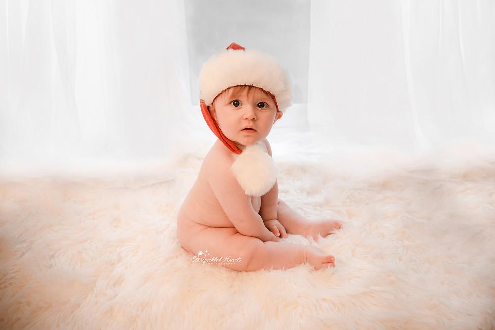 beautiful baby boy sitting on a white fluffy rug wearing a santa hat