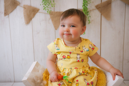 little girl pouting wearing yellow easter themed dress