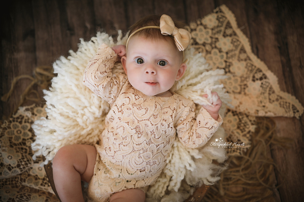 baby girl wearing a cream lacy romper, lying in a wooden basket filled with white blankets, on top of a creamy lacy rug