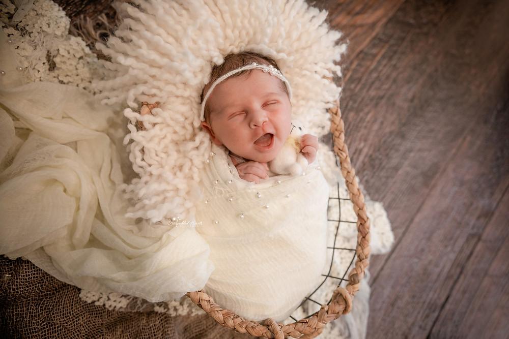 sleeping newborn baby girl lying in a wicker basket wearing all white