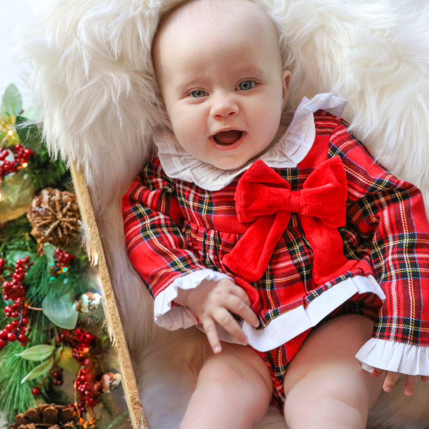 smiling sweet baby girl wearing red tartan christmas outfit with big red bow and peter pan collar, lying down in a brown wooden crate stuffed with a white fluffy rug