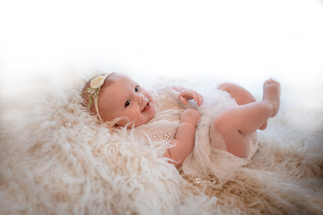 baby girl wearing a white lacy romper, lying on a white fluffy rug