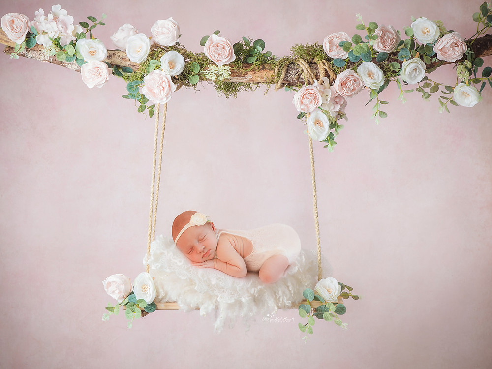 newborn baby girl lying on a swing, surrounded by pink and white flowers