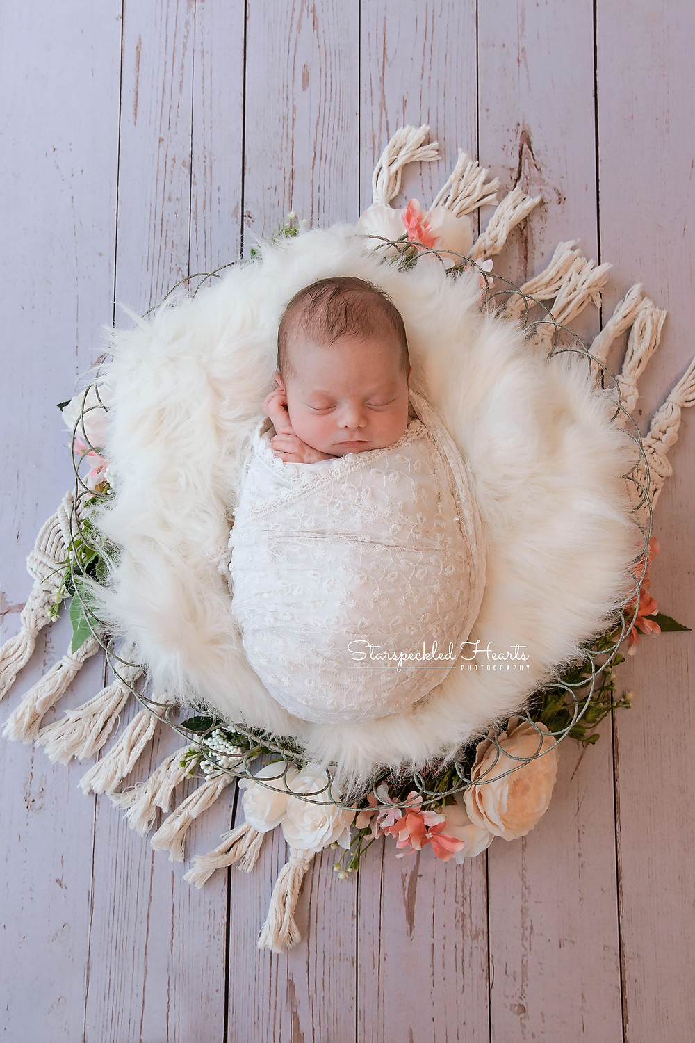 swaddled sleeping newborn girl lying in a basket surrounded by pink flowers and greenery for her newborn session in reading with starspeckled hearts photography