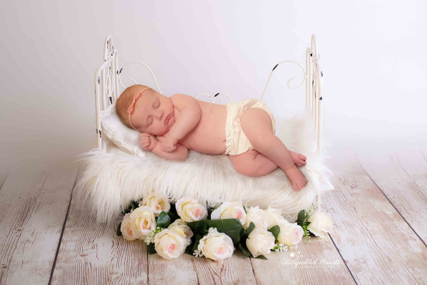 sleeping baby girl laying on her side on a white bed with flowers on the floor