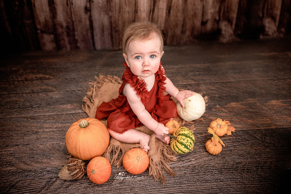 beautiful baby girl with big blue eyes, sitting on a dark wooden floor surrounded by pumpkins