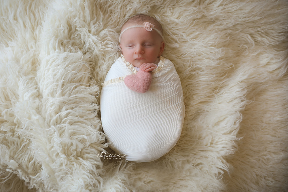 sleeping newborn girl in white, holding a pink felted heart in her hands, laying on a fluffy white rug