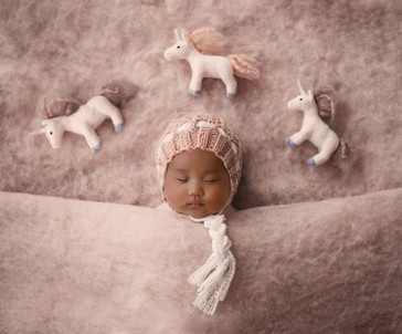 beautiful newborn girl wearing a pink knitted bonnet, laying underneath three white and pink unicorns