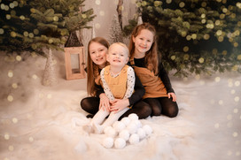 three sisters wearing matching outfits, sitting on a snowy floor all smiling at the camera