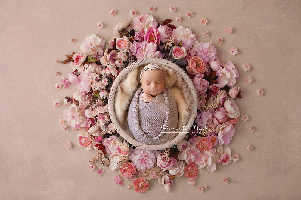 newborn baby girl wrapped in purple lying in a basket surrounded by pink flowers for her newborn photography session in aldershot