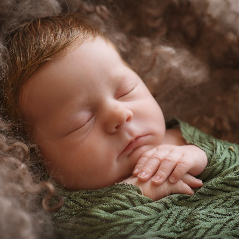 sleeping newborn girl in green with hands folded
