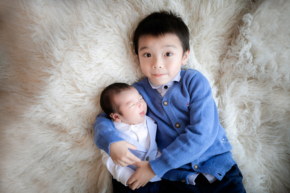 two brothers lying on a white fluffy rug both wearing blue