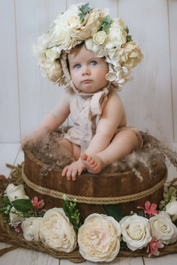 sweet little girl wearing a large flower bonnet, sitting in a brown circular bowl surrounded by white flowers