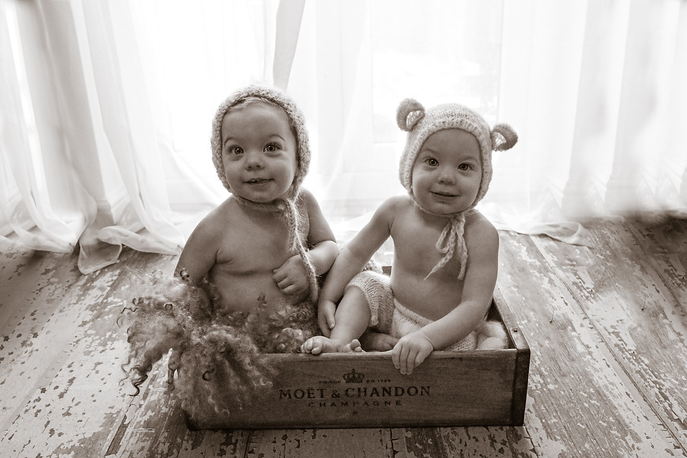 stunning twin baby boys wearing knitted bonnets, sitting in a wooden crate