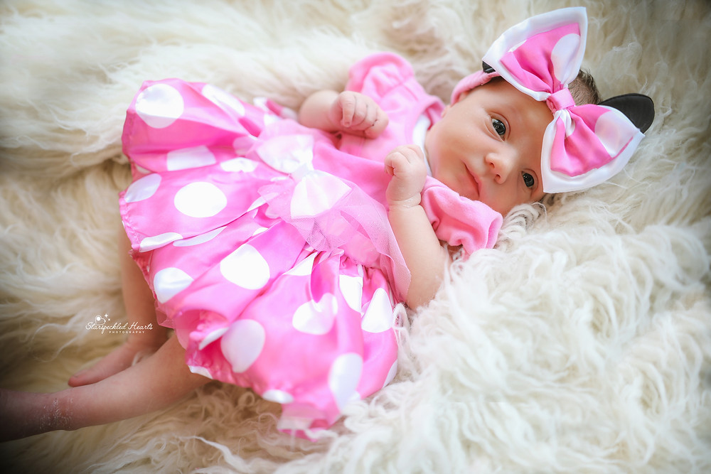 sweet newborn baby girl with eyes wide open, wearing a pink polkadotted dress and a large matching bow