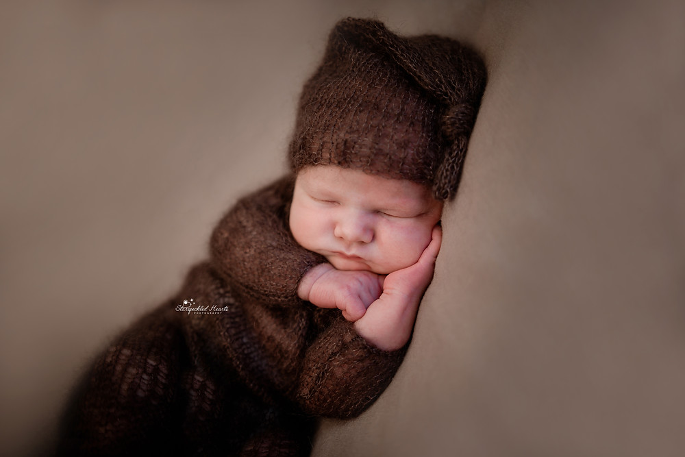 newborn photography session in hampshire of a newborn baby wearing a brown romper with a matching sleepy cap