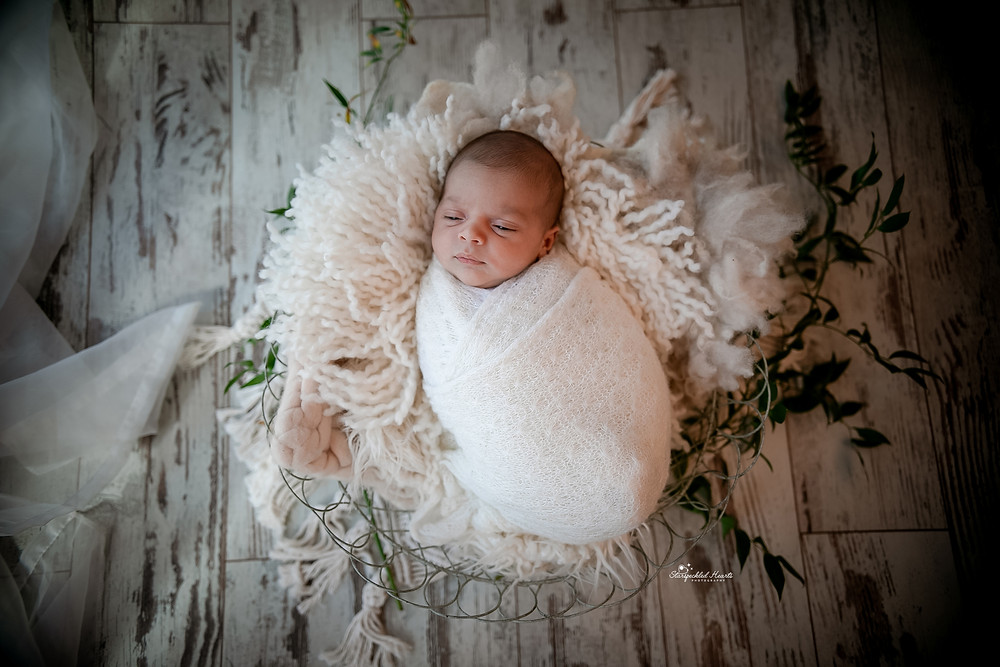 sleeping newborn wrapped in white, lying in a basket surrounded by leaves