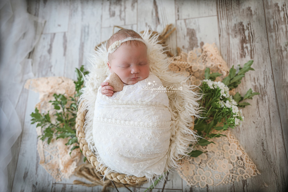baby girl wrapped in lace laying in a wicker basket surrounded by flowers and greenery