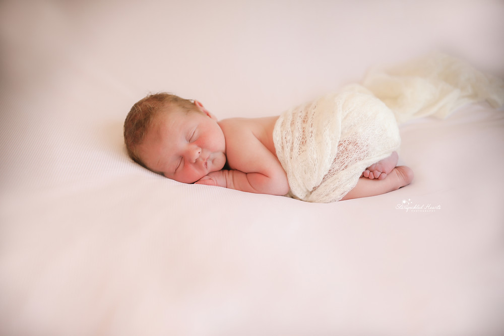 adorable sleeping newborn baby bum up pose, with a white knitted wrap tucked around his nappy
