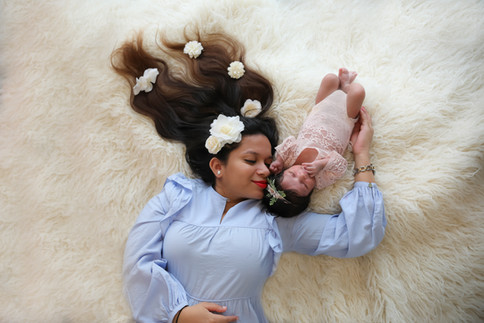 mother and baby lying together on a white furry rug