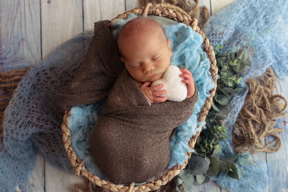 sleeping newborn baby boy holding a large white felted heart with both hands underneath his chin, wrapped in a brown wrap, laying in a wicker bowl stuffed with blue fluff