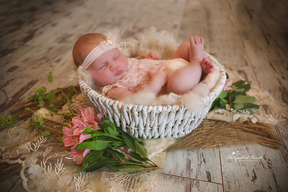 sleeping newborn wearing pink lace romper, lying in a white wicker bowl surrounded by flowers