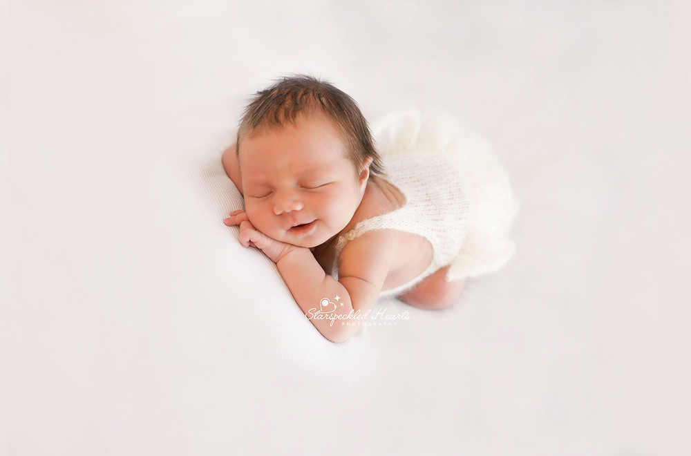 sleeping newborn baby girl lying on her tummy