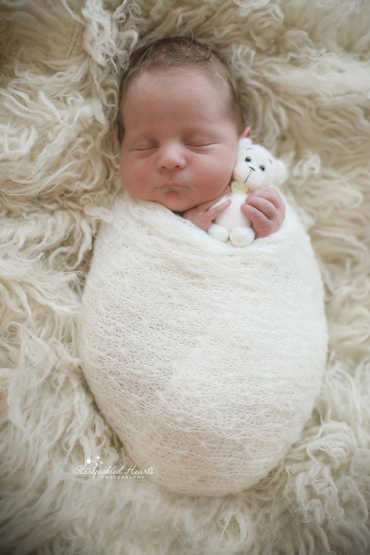 sleeping newborn baby boy, lying on a white rug cuddling a little white teddy