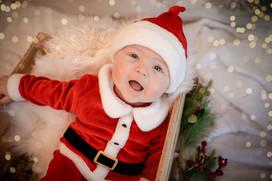 cute baby boy wearing a santa outfit, looking up at the camera