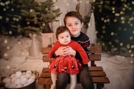 a big brother holding his baby sister on his lap, both wearing christmas outfits
