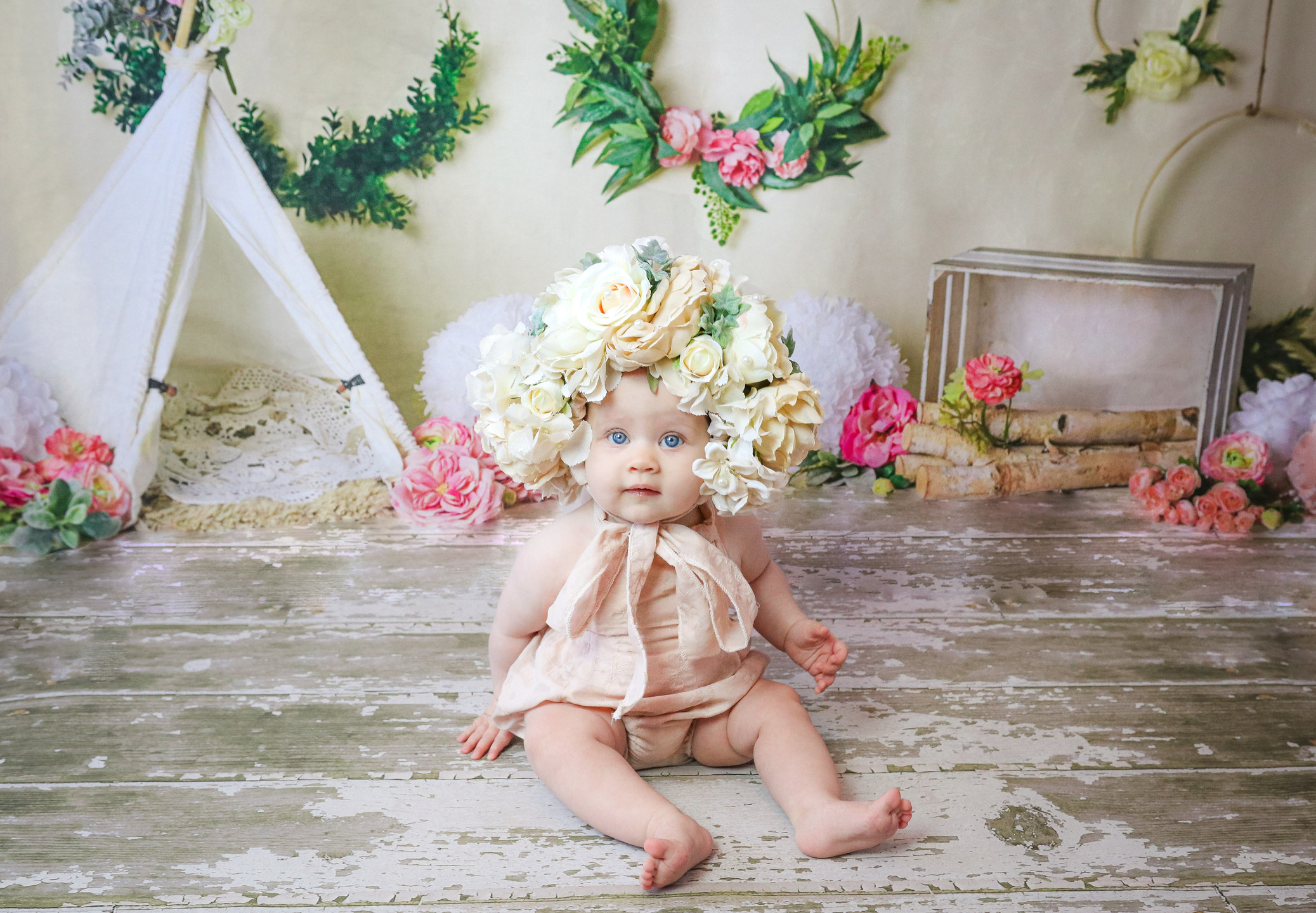 gorgeous baby girl wearing a large flower bonnet, sitting on wooden floor in front of a large white tent with flower wreaths on the wall