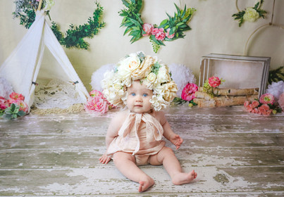 beautiful little girl with big blue eyes wearing a large flower bonnet and pale pink romper, sitting down on wooden floor in front of a small white tent and flower wreaths on the wall behind her
