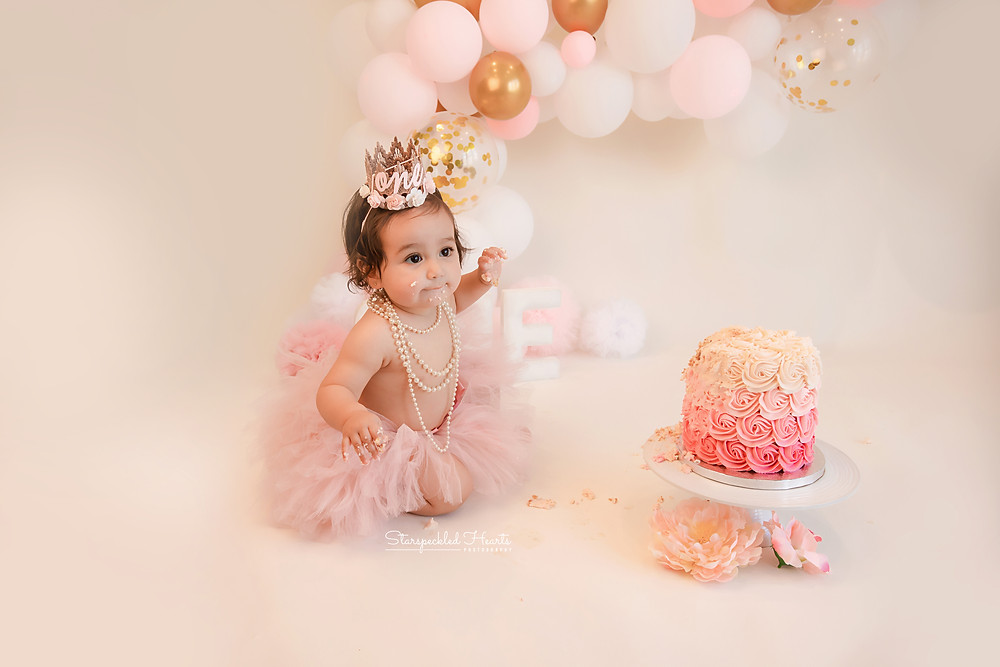 smiling baby girl wearing a pink tutu and pearls for her pink and gold themed cake smash session in hampshire