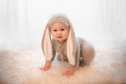 baby boy in a grey bunny outfit with long ears