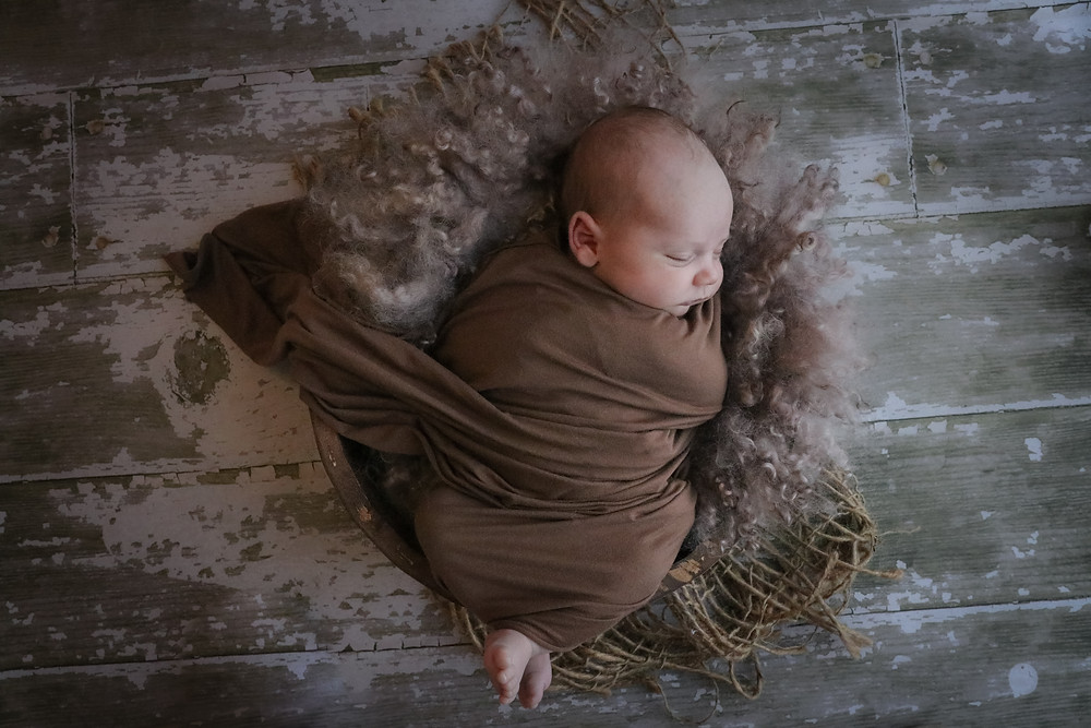 sleeping newborn baby boy wearing brown