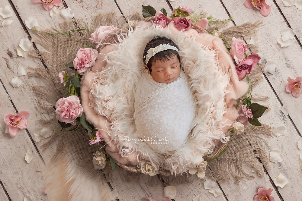 newborn baby girl swaddled in a white lace wrap lying in a basket surrounded by pink flowers in a boho style