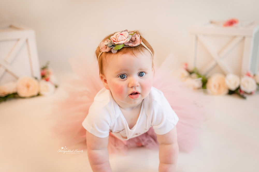 adorable baby girl wearing a pink floral headband and matching tutu for her cake smash and splash session in aldershot, hampshire