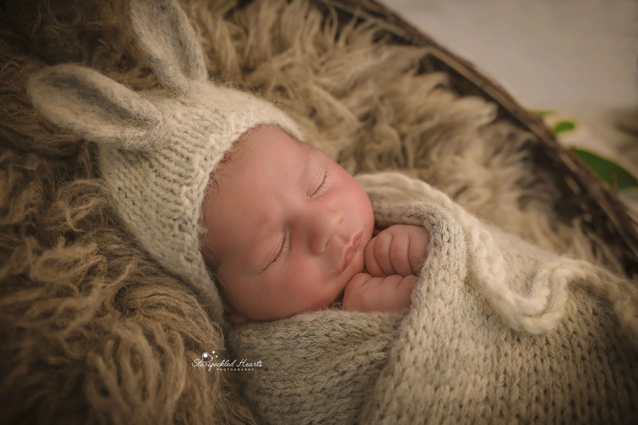sleeping baby boy wearing a grey knitted bunny bonnet, holding his fists up underneath his chin