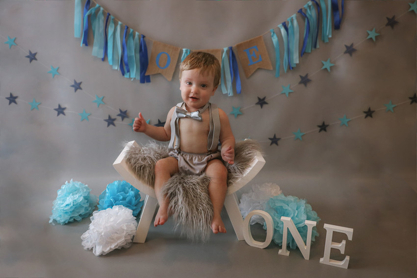 little boy wearing suspenders and shorts sitting on chair birthday theme