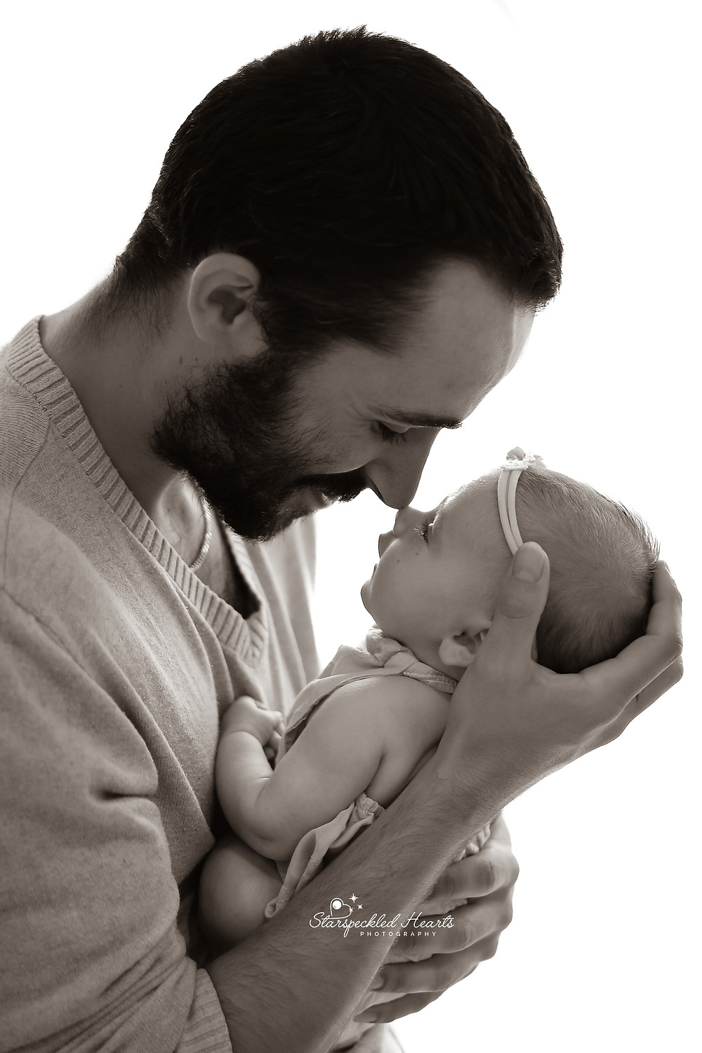 father holding his newborn baby girl up to his face, silhouetted black and white