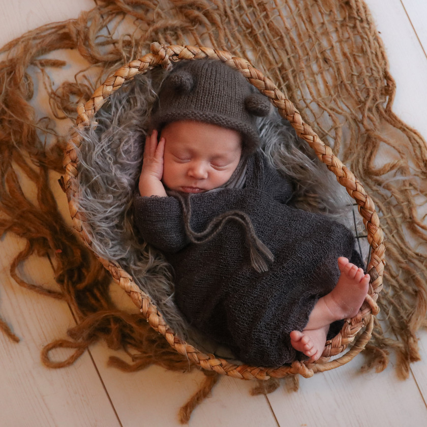 sleeping newborn laying in basket wrapped in grey