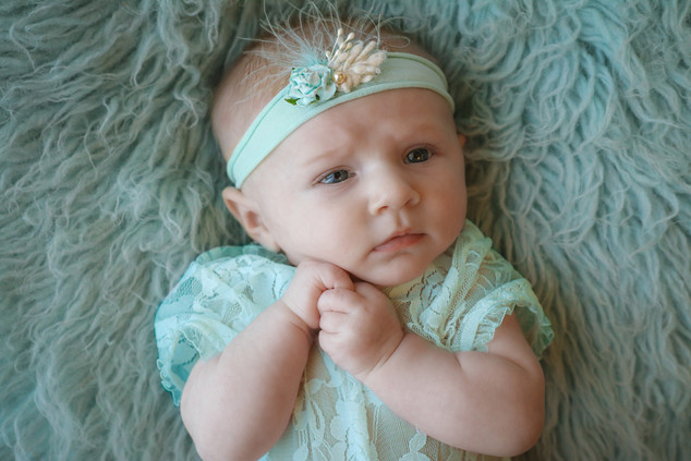 little girl wearing turquoise lace romper and headband
