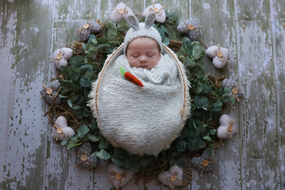 sleeping newborn wearing grey bunny bonnet laying in a basket surrounded by greenery