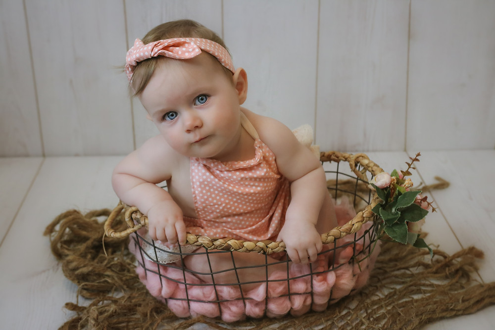 wide eyed baby girl wearing a pink polka-dotted romper and headband, sitting in a wicker wire-mesh basket on a hessian jute rug