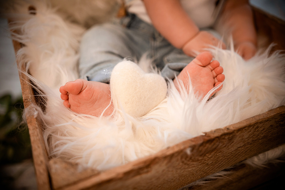 close up of baby toes with a felt heart in between his feet