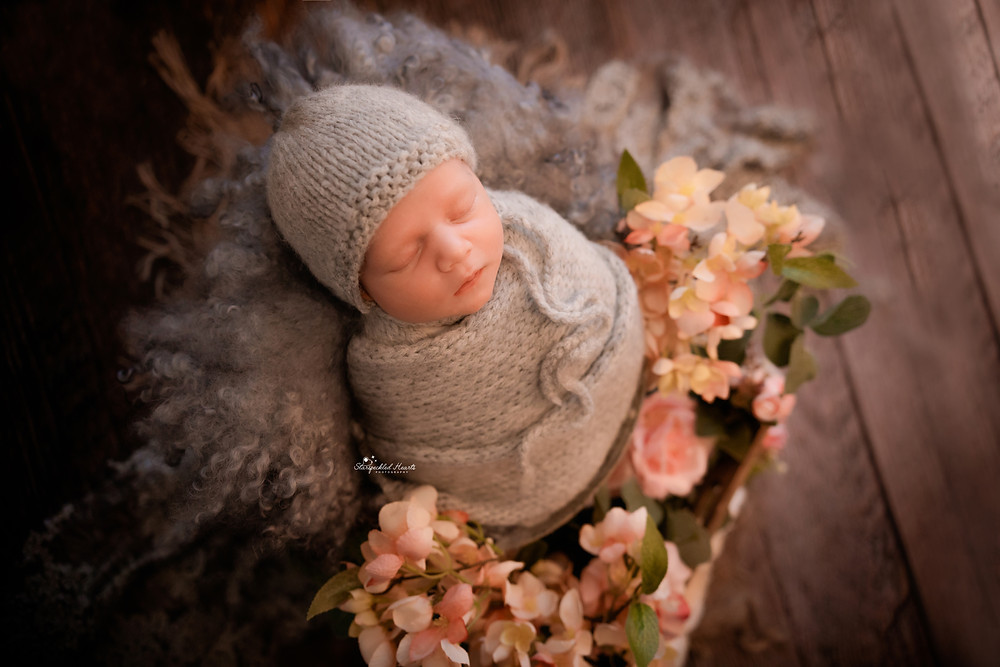 newborn baby girl wrapped in grey, surrounded by pink flowers