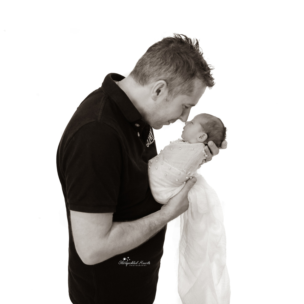 man holding a newborn baby girl up to his face