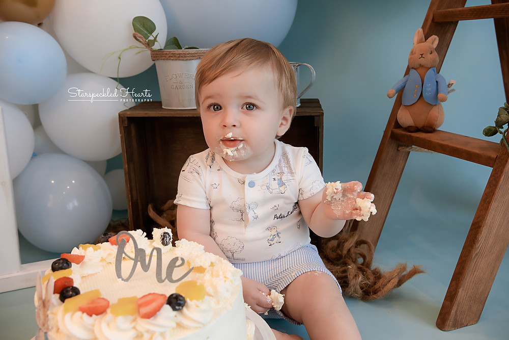 baby boy with cake around his mouth for his cake smash session with starspeckled hearts photography in aldershot hampshire