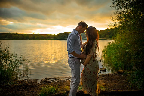 outdoor sunset maternity session with pregnant woman and her husband looking out over a large lake in hampshire